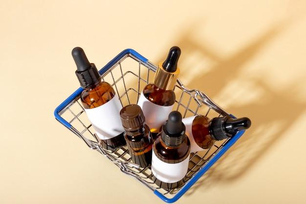Zestaw kosmetyków z zakraplaczem do pielęgnacji skóry twarzy w wózku sklepowym na żółtym tle z cieniami. koncepcja kupowania kosmetyków, zakupów online