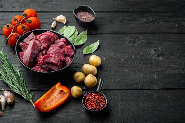 Zestaw kostek świeżej surowej wołowiny i ziemniaki, na czarnym drewnianym tle, z miejscem na kopię tekstu