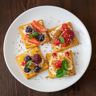 Zestaw krakersów z bliska różnych owoców na białym talerzu. widok z góry.