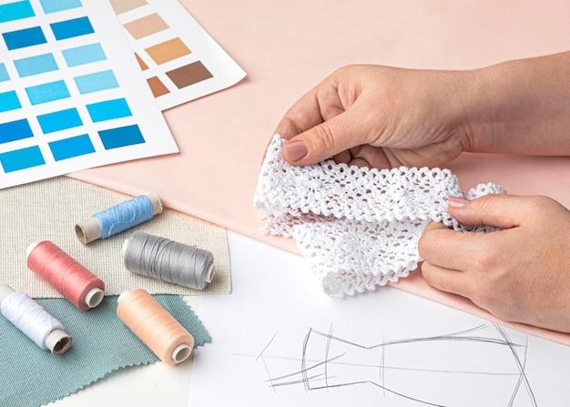 Zestaw krawiecki o dużym kącie z próbkami tkanin i nicią