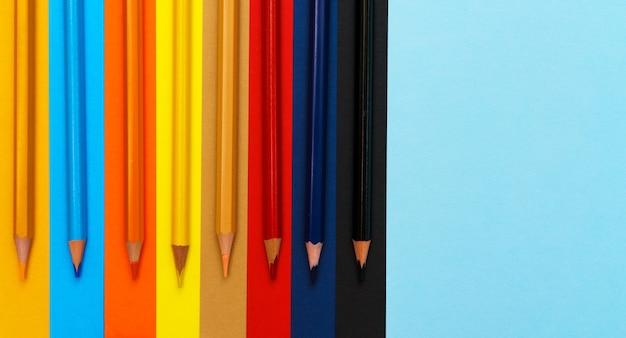 Zestaw kredek na kolorowym tle grupa drewnianych kredek do rysowania bryg...