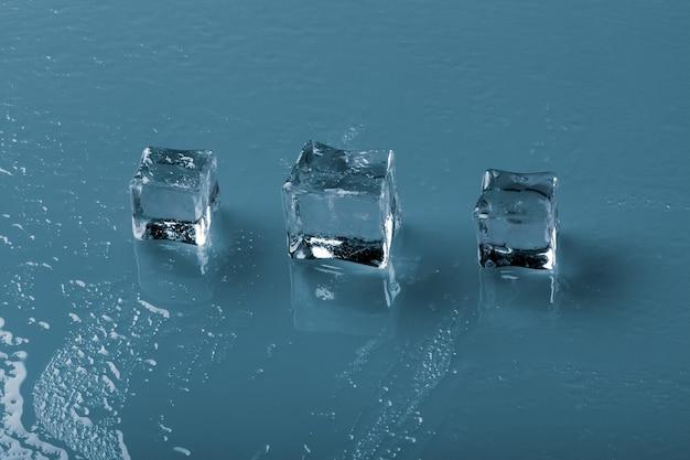 Zestaw krystalicznie czystych kostek lodu na niebieskim tle