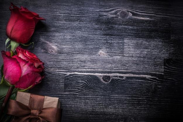 Zestaw kwitnących pachnące pączki róży pakowane pudełko na drewniane tła