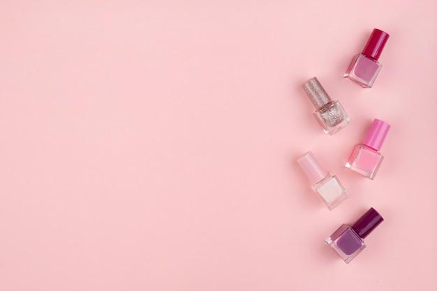 Zestaw lakierów do paznokci i kwiatów na różowej ścianie. pojęcie piękna, mieszkanie leżało z miejscem na tekst.
