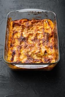 Zestaw lasagne z pieczonym mięsem, w blasze do pieczenia, na czarnym kamiennym tle