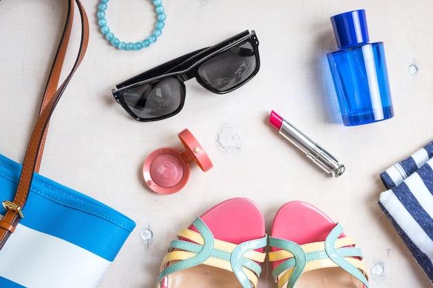 Zestaw letnich akcesoriów damskich: okulary przeciwsłoneczne, buty, kapcie, paszport, torebka w niebieskie paski, różowa szminka, rumieniec, perfumy na białym tle drewna.