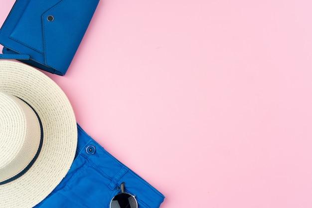 Zestaw letnich ubrań dla kobiety na różowej ścianie