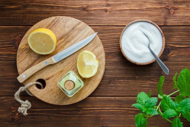 Zestaw liści, drewniany nóż, deska do krojenia, miska soli i połówka cytryny na drewnianej powierzchni. widok z góry.