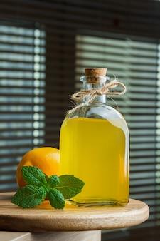 Zestaw liści i cytryny oraz butelka soku z cytryny na czarnej powierzchni okna. widok z boku.