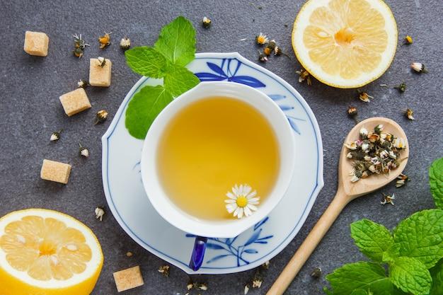 Zestaw liści mięty, cukru, cytryny i ziół rumianku w łyżce i filiżance herbaty rumiankowej