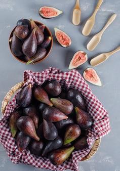 Zestaw łyżek i mis fig i połówek w koszu piknikowym i misce na szarym tle. widok z góry.