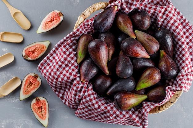 Zestaw łyżek i mis fig i połówek w koszu piknikowym na szarym tle. widok z góry.