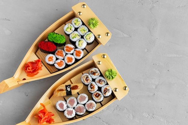 Zestaw maki sushi na drewnianej tacy łodzi z bliska