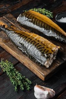 Zestaw makreli wędzonej ryby, na starym ciemnym drewnianym stole