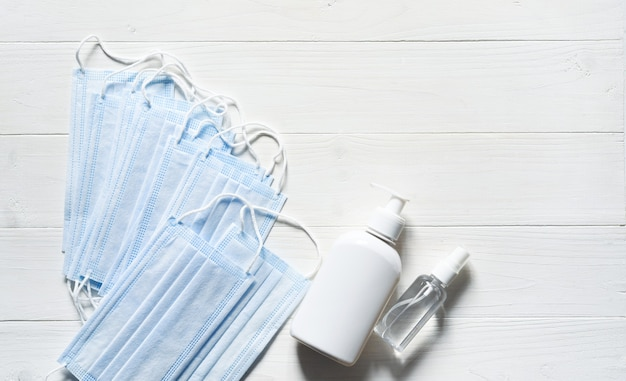 Zestaw masek, mydła i środka antyseptycznego na białym tle drewnianych. medycyna i opieka zdrowotna. karatnin.