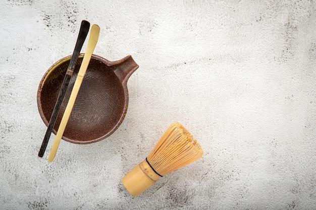 Zestaw matcha bambusowa trzepaczka do matchy i miarka do herbaty chashaku na białym betonie.