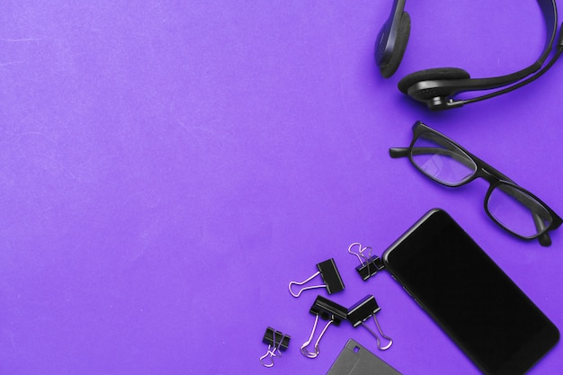 Zestaw materiałów biurowych na fioletowym tle, widok z góry