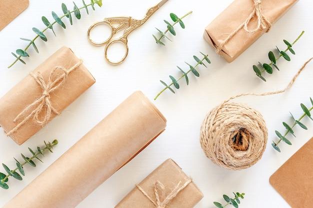Zestaw materiałów do pakowania prezentów świątecznych. papier siarczanowy, sznurek jutowy, nożyczki, pudełka i gałązki zielonego eukaliptusa