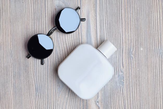 Zestaw męskich perfum i okularów przeciwsłonecznych na drewnianym stole. widok z góry.