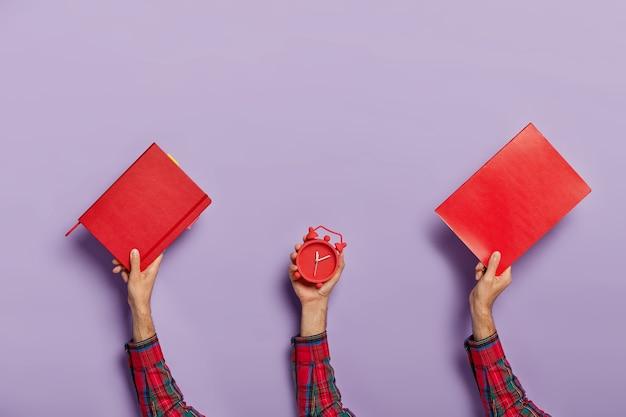 Zestaw męskich rąk nosi czerwony notatnik, podręcznik i budzik