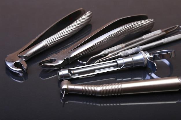 Zestaw metalowych narzędzi medycznych do pielęgnacji zębów na czarnym lustrze. selektywne ustawianie ostrości.
