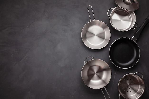 Zestaw metalowych patelni kuchennych. przybory kuchenne, książka kucharska i koncepcja lekcji gotowania