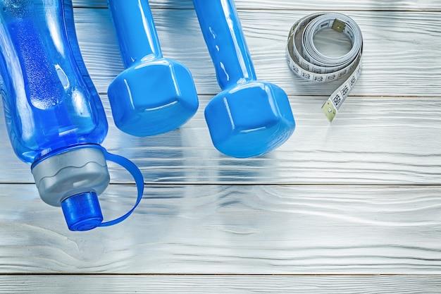 Zestaw miarka butelka wody niebieskie hantle na drewnianej desce koncepcja fitness