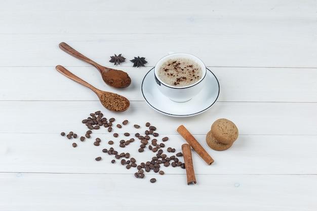 Zestaw mielonej kawy, przypraw, ziaren kawy, ciasteczek i kawy w filiżance na podłoże drewniane. widok pod dużym kątem.