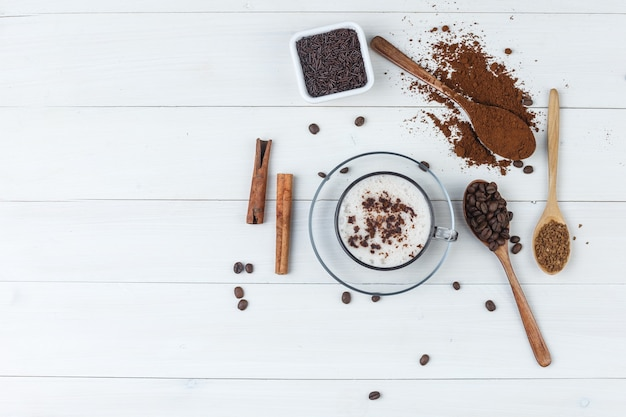 Zestaw mielonej kawy, ziaren kawy, lasek cynamonu i kawy w filiżance na podłoże drewniane. widok z góry.