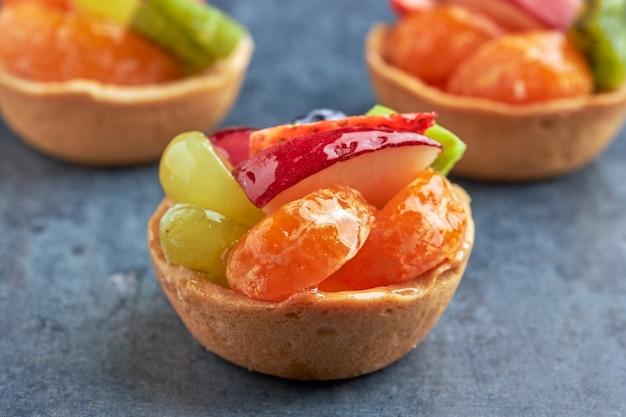 Zestaw mini deserów ze świeżych owoców premium premium na biszkopcie na drewnianym stole.