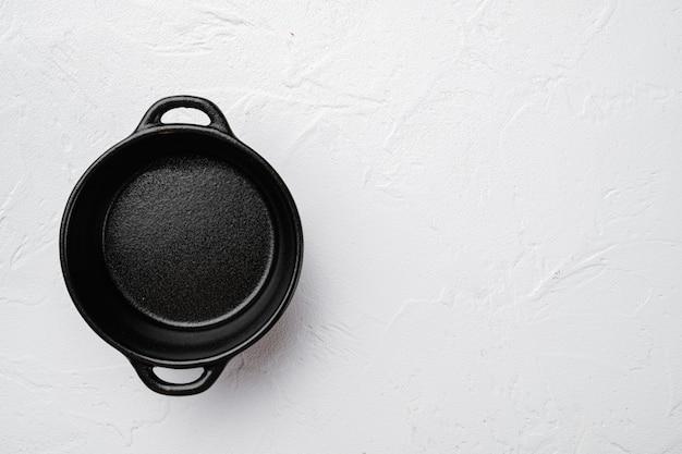 Zestaw misek czarnej ceramiki, z miejscem na kopię na tekst lub jedzenie, z miejscem na kopię na tekst lub jedzenie, widok z góry płasko leżał, na białym tle kamiennego stołu