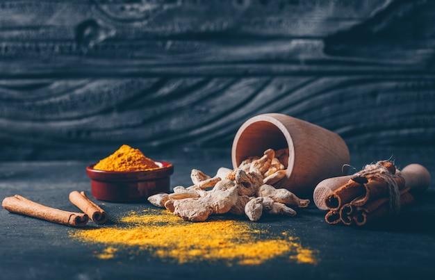 Zestaw młynek do ziół, imbir i suchy cynamon i imbir w proszku w filiżankach herbaty na ciemnym tle z teksturą. widok z boku. miejsce na tekst
