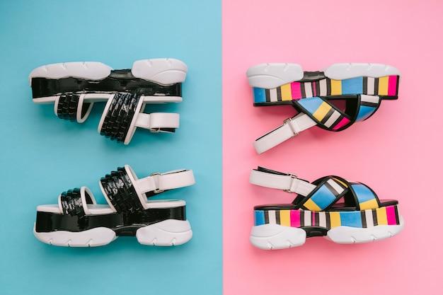 Zestaw modnych kobiecych butów. letnie modne, wielokolorowe damskie sandały na wysokim klinie na niebiesko-różowej ścianie. voguish i stylowe obuwie dla nowoczesnych dziewczyn.