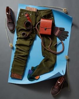 Zestaw mody i akcesoriów mans na niebieskim papierze i czarnej betonowej ścianie