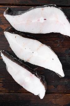 Zestaw mrożonych steków rybnych, na starym ciemnym tle drewnianego stołu, widok z góry płaski lay