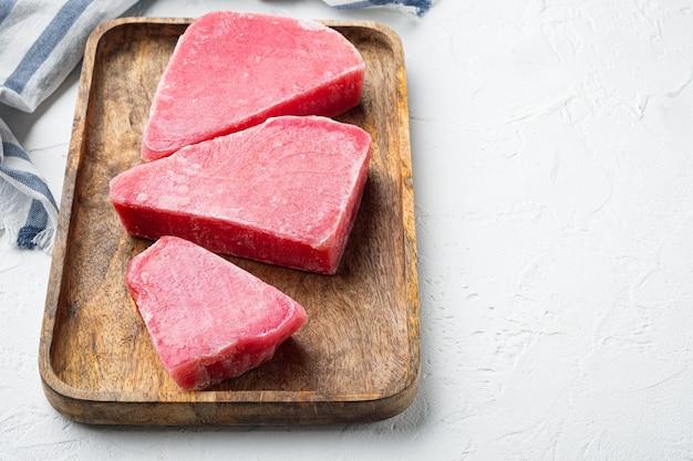 Zestaw mrożonych steków z tuńczyka, na drewnianej tacy, na białym kamieniu
