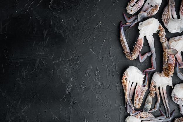Zestaw mrożonych surowych, niebieskich krabów pływających na czarnym stole, płaski widok z góry