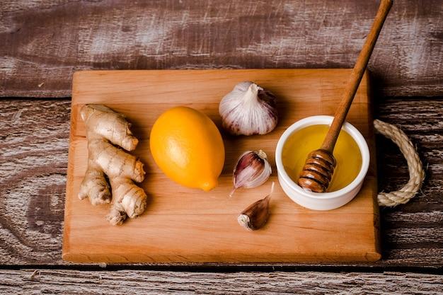 Zestaw na odporność, witamina c-miód, korzeń imbiru, cytryna, czosnek, na desce, brązowe tło