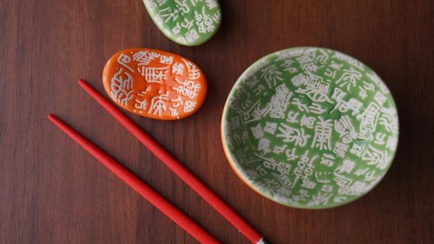 Zestaw naczyń ceramicznych do sushi i czerwonych paluszków sushi na drewnianym tle