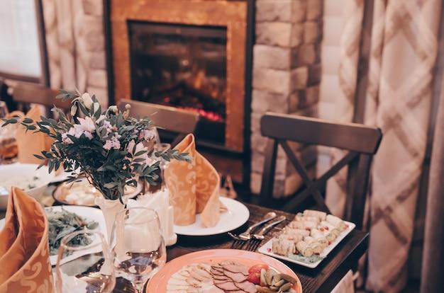 Zestaw nakryć do imprezy. drewniany stół przy kominku