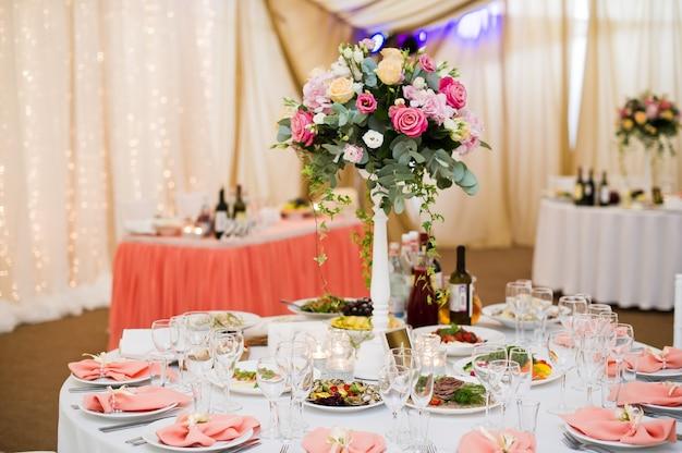 Zestaw nakryć na bankiecie weselnym w restauracji, klasyczny styl z białymi obrusami i serwetkami, wazony z kwiatami.