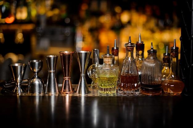 Zestaw narzędzi barmana, w tym osadzarki i małe butelki z alkoholem