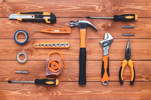 Zestaw narzędzi budowlanych na drewnianym tle. młotek, klucz, szczypce i śrubokręt. karta podarunkowa na świąteczne święto pracy, dzień ojca. sprzęt, miejsce pracy. leżał płasko. koncepcja diy.