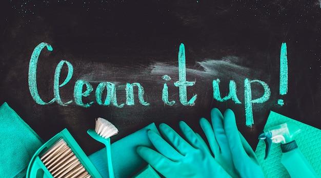 Zestaw narzędzi do czyszczenia domu pod napisem na tablicy.