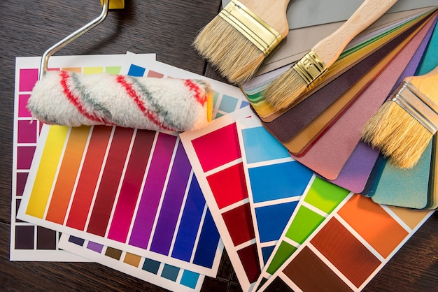 Zestaw narzędzi do malowania jako przewodnik po palecie kolorów, niebieskie rękawiczki i pędzel na drewnianej desce