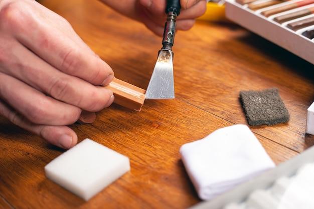 Zestaw narzędzi do renowacji laminatu i parkietu do drewna, ołówki woskowe, uszczelniające zarysowania i wióry z bliska.