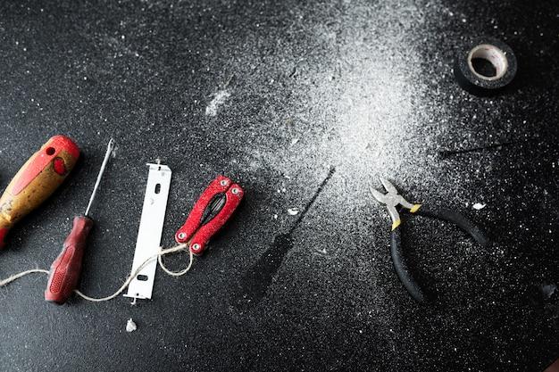 Zestaw narzędzi do samodzielnego montażu lampy leży na czarnym stole, posypanym białym pyłem do prac domowych.