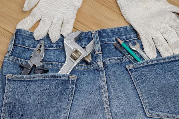 Zestaw narzędzi domowych do prac naprawczych w kieszeniach jeansów. ścieśniać