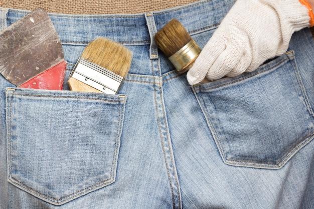 Zestaw narzędzi domowych do prac naprawczych w kieszeniach jeansów. stare i zakurzone narzędzia. ścieśniać