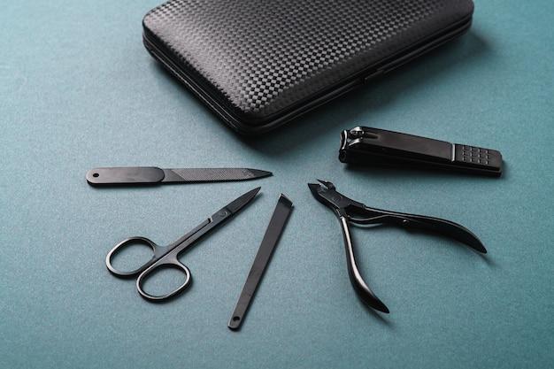 Zestaw narzędzi i akcesoriów do manicure i pedicure, blisko etui, kąt widzenia, niebieskie tło